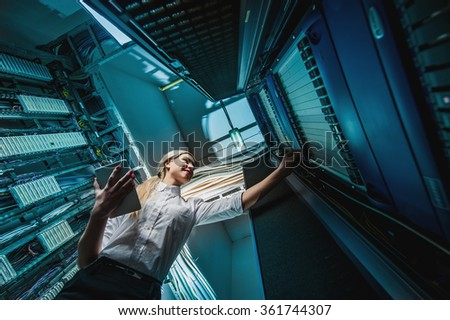 Young engineer businesswoman in server room