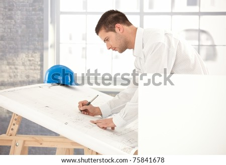 Young engineer busy by working, using drawing table.?