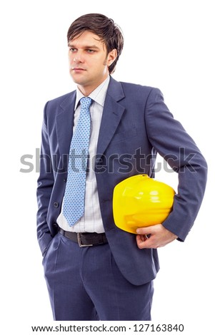Young engineer holding a helmet under his arm against white background