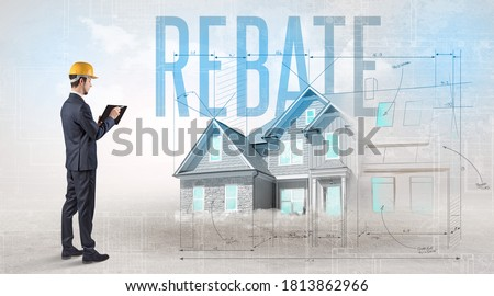 Young engineer holding blueprint with REBATE inscription, house planning concept Stock photo ©