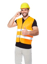 Young engineer in a reflective vest with yellow helmet calling by phone