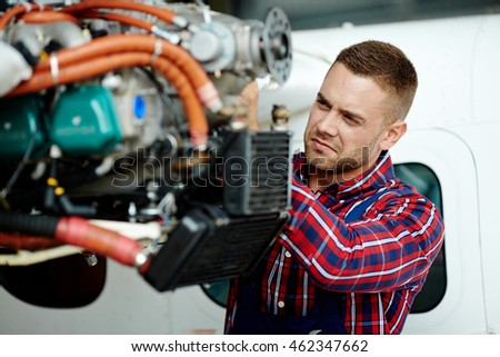 Young engineer repairing part of airplane #462347662