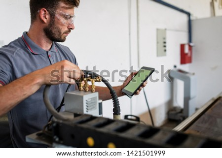 Young engineer setup plasma cutter for work in metalwork workshop.
