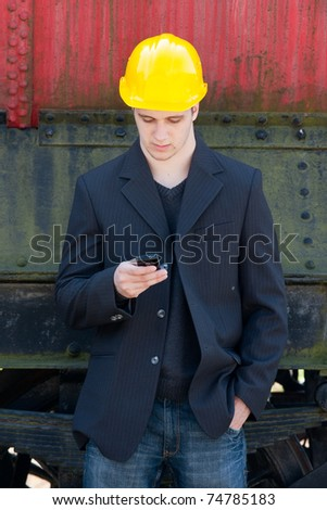 young engineer standing in front of old train