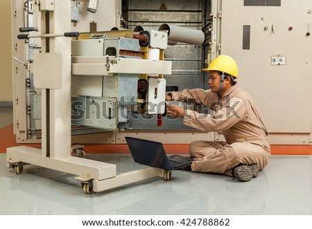 Young engineer to check the breaker with a computer #424788862