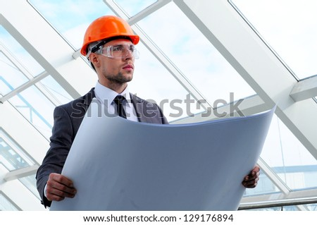 Young engineer with paper plans