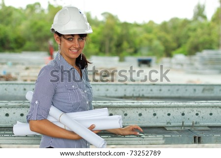 young engineer woman standing with rolled drawings in the warehouse