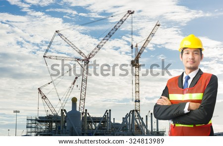 Young engineering man and safety helmet, shirts standing arms crossed against the mountains building