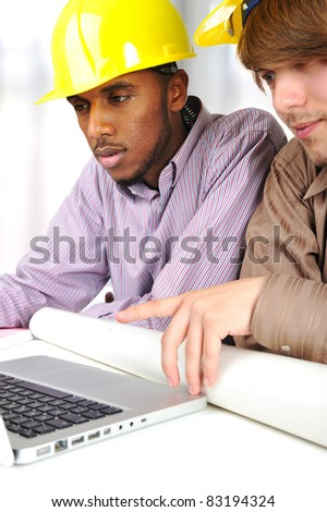 Young engineers, african and caucasian working together