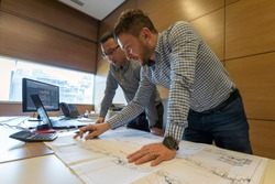Young engineers are reviewing construction on the engineering drawing project. Engineers, as practitioners of engineering, are professionals who invent, design, analyze, build and test machines.