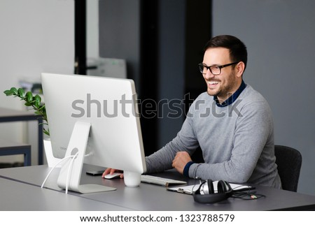 Young enthusiastic entrepreneur who loves his job. Smiling while working at his desk at the office in front of a monitor.