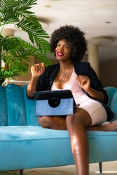 Young entrepreneur of black race and afro hair making a video call of a work meeting, black jacket and pink dress, teleworking, new normal, sitting on a blue sofa in a hotel