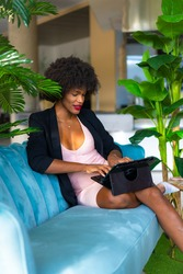 Young entrepreneur of black race and afro hair making a video call of a work meeting, black jacket and pink dress, teleworking, new normal, sitting on a blue sofa and some green plants in a hotel