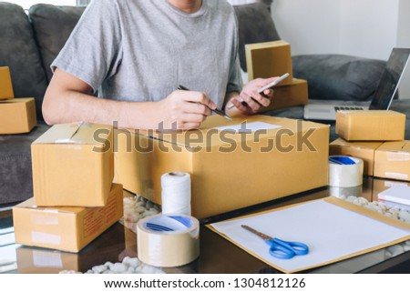 Young entrepreneur SME freelance man using smartphone receive order client and take note working with packaging sort box delivery online market on purchase order and preparing package product.