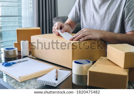 Young entrepreneur SME man receive order client and working with packaging sort box delivery online market on purchase order and preparing package product, Small business parcel for shipment. Stock photo ©