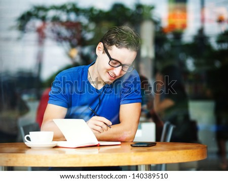 Young entrepreneur working in a cafe (soft focus)