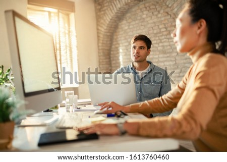 Young entrepreneur working on laptop while being on a meeting with female coworker in the office.