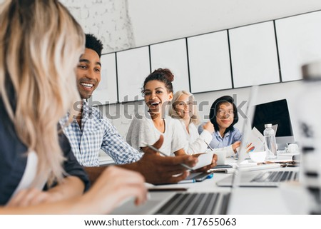 Young entrepreneurs discussing something with smile during conference. Indoor portrait of international employees sitting in office with laptops and talking about work.