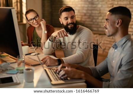 Young entrepreneurs working late and communicating in the office. Focus is on man with beard.