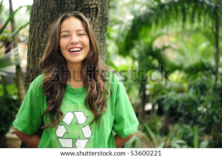 young environmental activist  in the forest wearing a green recycle t-shirt