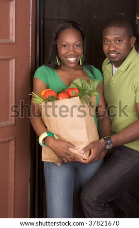 Young ethnic African American couple coming back home, returning from store with paper bag full of vegetables