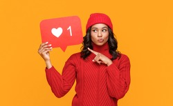 Young ethnic female showing banner with like symbol and keeping finger near lips while sharing secret in social media against yellow background
