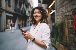 Young ethnic woman with smartphone smiling and standing on street and browsing internet wearing casual clothes on sunny day looking forward