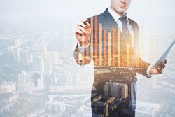 Young european businessman with document in hand drawing abstract business chart on city background with copy space. Finance concept. Double exposure