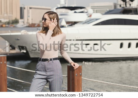 Young european female standing near big yacht. Woman in a beige turtleneck and trousers, casual or smart casual sryle. Marina or port #1349722754