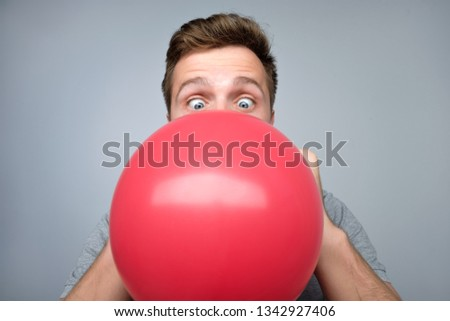 Young european man blowing up a red balloon preparing for party on gray background Сток-фото ©
