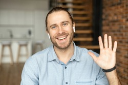 Young European man looking at the camera, smiling and waving the hand, positive person with bewitching smile, say hi, with white earphones, greeting family or friends by video, wearing blue shirt