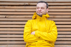 young European man with sly smile sitting outside on wooden bench in bright yellow jacket with crossed hands, thinking over idea, plan, looking aside, cunning look, dreaming or imagining something