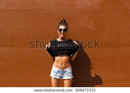 Stock Photo Young European teenage brunette curly model posing near brown ribbed wall, grimacing, jumping, wearing blue jeans mini shorts, sneakers, round sunglasses and black t-shirt, ready to party