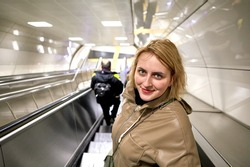Young European woman descends on an escalator to subway station.