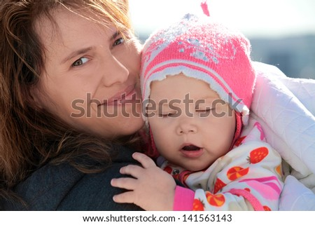 Young European woman holds her sleepy baby girl in blanket. Outdoor closeup portrait