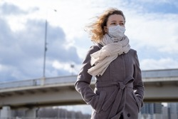 young European woman in protective disposable medical mask walking  in deserted city street outdoor. concept of coronavirus influenza covid-19 quarantine and people panic. apocalypse sky