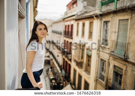 Young european woman spending free time home.Self care,staying home.Enjoying view on the balcony.Relaxing at home.Hotel room balcony view,vacation in Europe.Narrow street in Granada,Andalucia,Spain.
