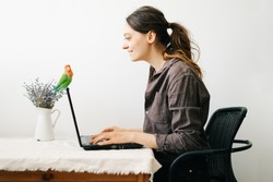 young European woman, working from home during the virus quarantine, on her laptop.a small green lovebird parrot sits on a laptop monitor.A cosy working place,the concept of remote work. freelance