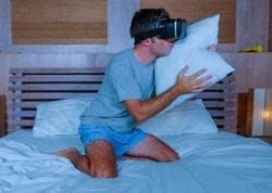 young excited and aroused man at home wearing 3d virtual realty goggles having fun on bed playing alone with internet cyber sex VR simulator kissing pillow in sexual illusion and desire concept