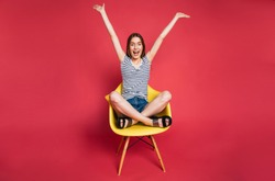 Young excited beautiful blonde woman in casual wear is sitting on yellow chair in big studio with pink background. Happy and funny stylish girl