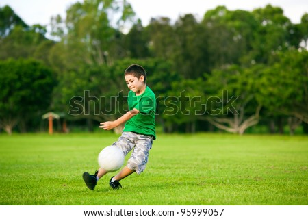 Young excited boy kicking ball in the grass outdoors