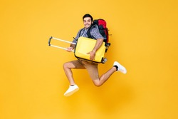 Young excited Caucasian male tourist with baggage jumping in mid-air ready to travel isolated on colorful studio yellow background
