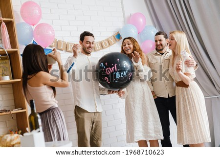 Young excited couple blowing up surprise balloon during gender reveal party indoors Сток-фото ©