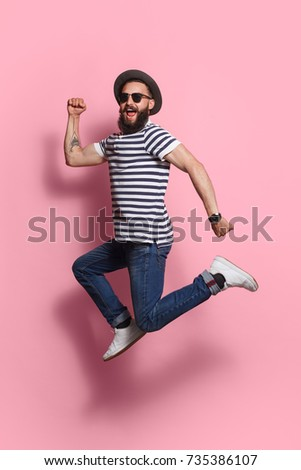 Shutterstock Young excited hipster man in gat and sunglasses jumping and posing on pink studio background.