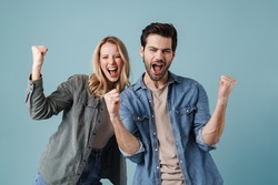 Young excited man and woman screaming and making winner gesture isolated over blue background