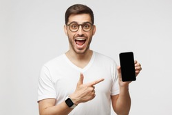 Young excited man in white t-shirt and glasses, pointing finger to blank screen of phone to viewer with WOW face, isolated on gray background