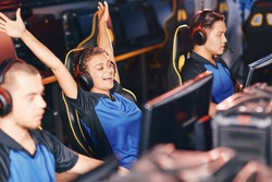 Young excited mixed race girl, female cybersport gamer wearing headphones raising hands up, celebrating success while participating in eSport tournament
