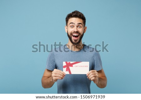Young excited surprised man in casual clothes posing isolated on blue wall background studio portrait. People sincere emotions lifestyle concept. Mock up copy space. Holding in hands gift certificate