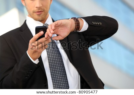 Young executive checking his watch against a cellphone
