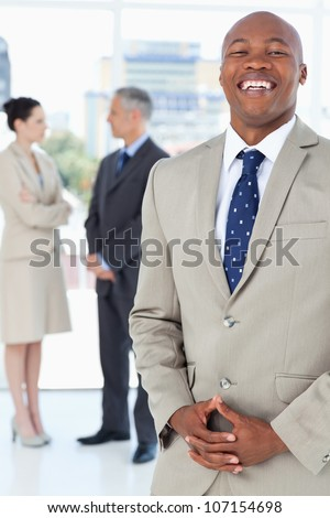 Young executive laughing while standing upright and crossing his hands
